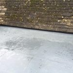 Flat roof with water on as part of an old looking house extension 3