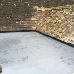 Flat roof with water on as part of an old looking house extension 2