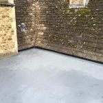 Flat roof with water on as part of an old looking house extension