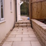 Light coloured stone path with steps at the end down the side of a cream house