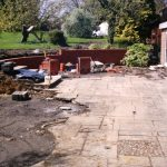Building a brick wall to separate the unfinished grey stone patio from the top grass