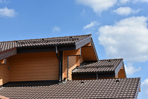 The top of a modern tiled roof on a wooden effect house